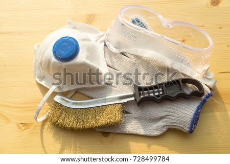Respirator, gloves, brush and glasses lying on the wooden surface. #728499784