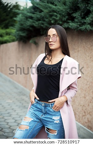 Young woman wearing coat and denim pants #728510917