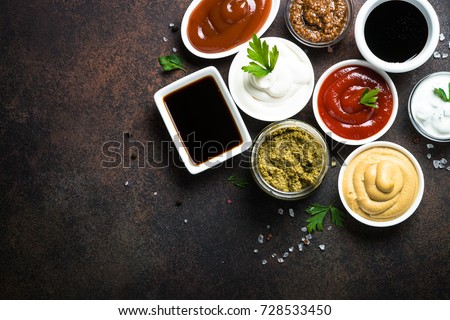 Set of sauces - ketchup, mayonnaise, mustard soy sauce, bbq sauce, pesto, mustard grains and pomegranate sauce on dark rusty stone or metal background. Top view. #728533450