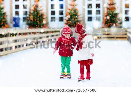 Kids ice skating in winter park rink.