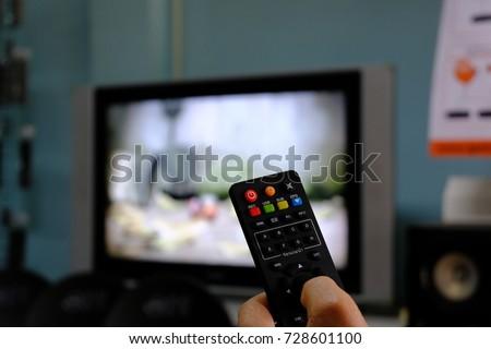 remote control satellite receiver box. blurred television background. #728601100