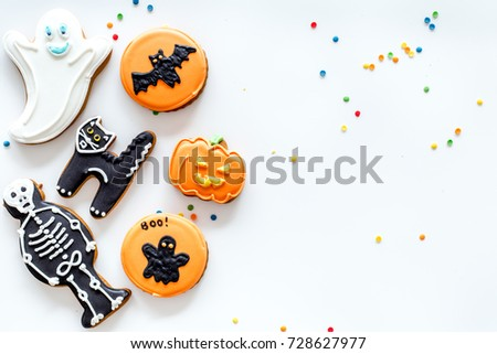 Halloween gingerbread cookies with pictures bat, pumpkin, skeleton, ghost on white background top view copyspace