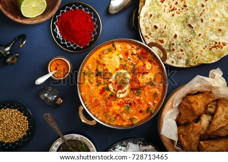Indian cuisine on diwali holiday: tikka masala, samosa, patties and sweets with mint chutney and spices. Dark blue background Royalty-Free Stock Photo #728713465