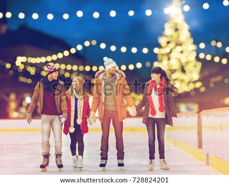 christmas, winter and leisure concept - happy friends holding hands on skating rink over outdoor holiday lights background