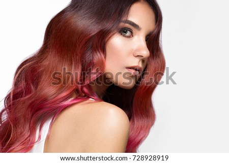 Beautiful pink-haired girl in move with a perfectly curls hair, and classic make-up. Beauty face. Picture taken in the studio.