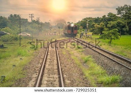 Trains were running through the intersection between the railway and automobile roads and motorcycles.. When the sun is setting. #729025351