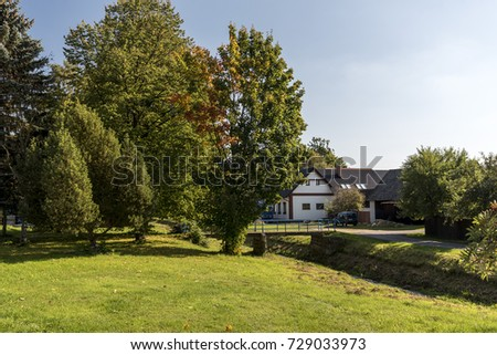 a white cottage near the creek and a tree with a colored leaf #729033973