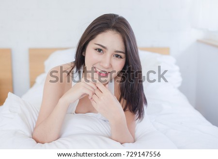 beautiful healthy woman smiling on bed #729147556