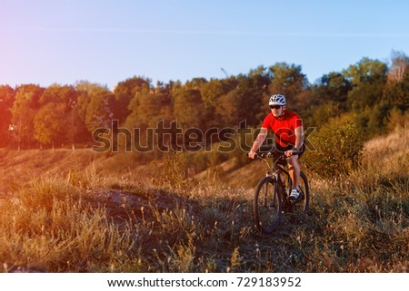 young bright man on mountain bike riding in autumn landscape #729183952