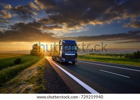 Blue truck driving on the asphalt road in rural landscape at sunset between dark clouds #729219940