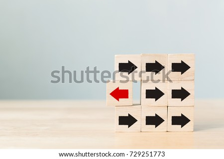 Wooden block with red arrow facing the opposite direction black arrows, Unique, think different, individual and standing out from the crowd concept Royalty-Free Stock Photo #729251773