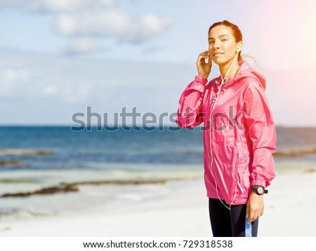 Sporty woman with earphones on the sea coast #729318538