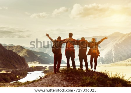 Four happy friends are looking on mountains and having fun together. Space for text. Travel concept #729336025