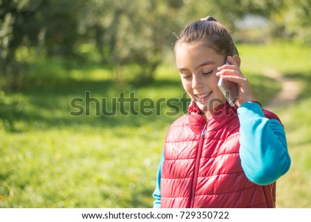 Beautiful girl talking on a smartphone in a red vest on the outdoor.Portrait smiles girl positive, emotion, happiness, smile. Young  girl receiving good news by phone.  #729350722