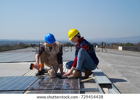 young engineer girl and an elderly skilled worker fitting a photovoltaic plant #729454438