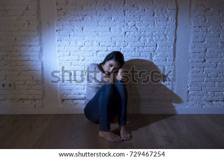 lonely young attractive Hispanic woman sitting at home floor frustrated suffering depression feeling sad and desperate with a headache in problems and broken heart concept #729467254