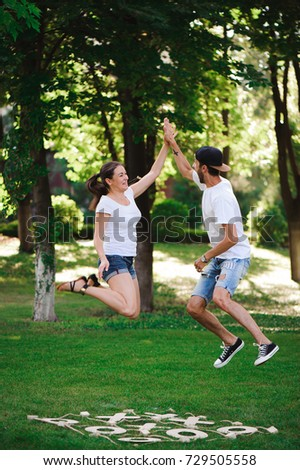 A young couple celebrate victory playing tic-tac-toe in the park #729505558
