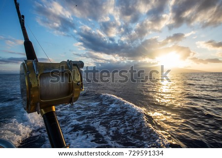 Deep Sea Fishing Reel on a boat during sunrise  Royalty-Free Stock Photo #729591334