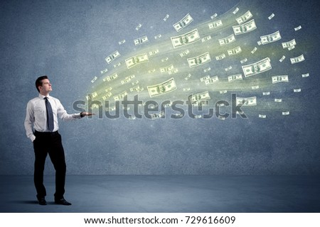 Caucasian male in business suit holding money,which flies through his hands #729616609