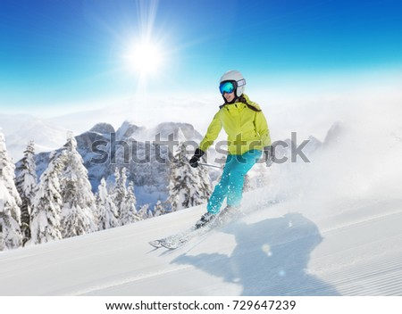 Young woman skier running down the slope in Alpine mountains. Winter sport and recreation, lesure outdoor activities. #729647239