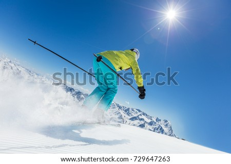 Young woman skier running down the slope in Alpine mountains. Winter sport and recreation, lesure outdoor activities. #729647263