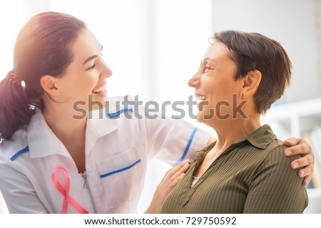 Pink ribbon for breast cancer awareness. Female patient listening to doctor in medical office. Raising knowledge on people living with tumor illness. Royalty-Free Stock Photo #729750592