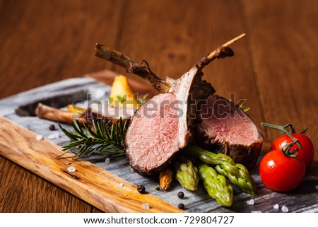 Baked lamb loin, served with asparagus. Dark background. #729804727