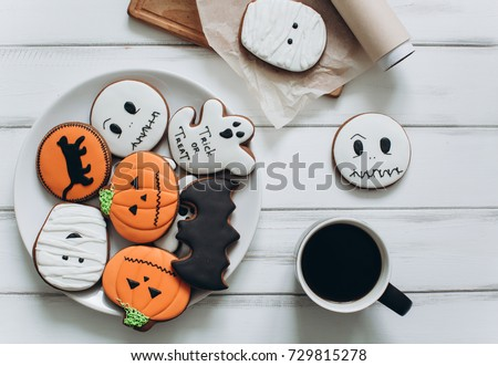Preparation for Halloween. Coffee and scary gingerbread cookies on a wooden background.