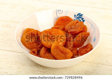 Dried apricots heap in the bowl over wooden background #729828496