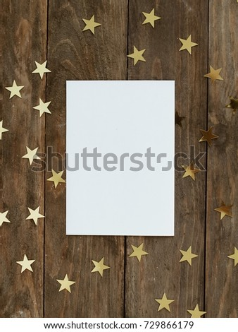 Mock up greeting card on wood rustic background with Christmas decorations glitter snowflakes and gold stars confetti. Invitation, paper. Place for text flat lay