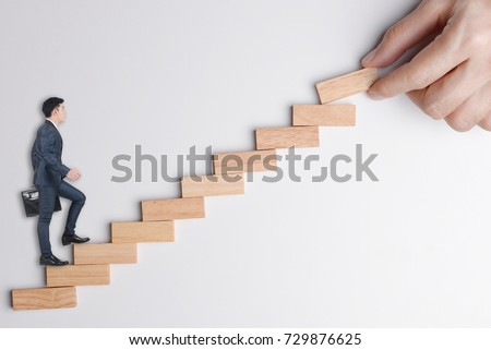 Businessman stepping up on stairway, following hand put wood block to make rising way to keep raising up or growing business. Abstract background to leader brings follower to success. #729876625