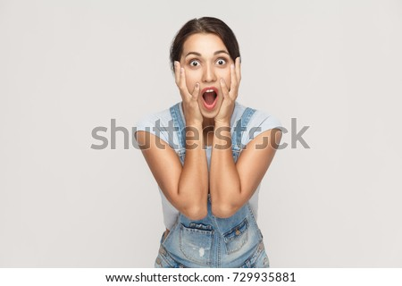 Human face expressions and emotions. Arab young adult woman holding arms on her cheeks and shocked. Isolated on gray background, studio shot