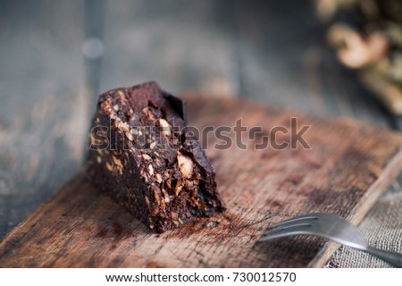 Raw chocolate brownies cake with hazelnuts on rustic wooden table. Dark food photography