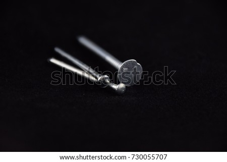 Closeup of different stainless steel nails against black background #730055707