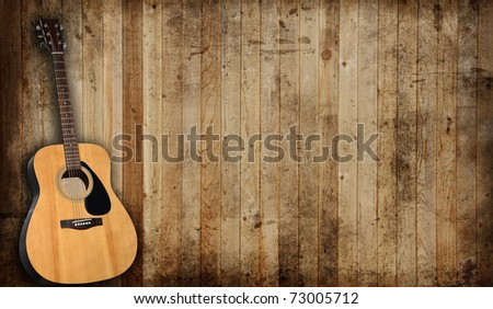 Acoustic guitar against an old barn background.