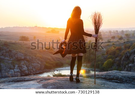 Woman in a witch costume with a broom and hat, a background of halloween. The witch looks at the sunset, free space. Royalty-Free Stock Photo #730129138