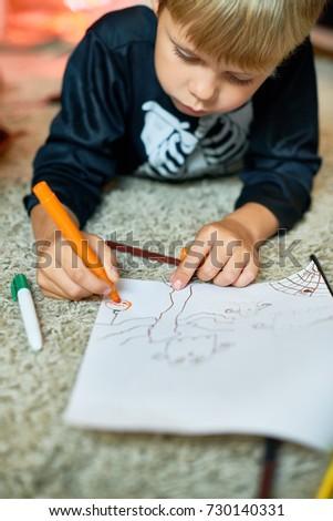 Portrait of cute little boy wearing Halloween costume drawing laying on floor #730140331