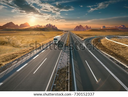 Single delivery truck driving from the mountain range towards the setting sun. Fast motion drive on the straight freeway in beautiful landscape. Freight scene on the empty motorway. Royalty-Free Stock Photo #730152337
