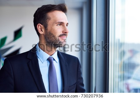Smiling businessman standing in office and looking through window Royalty-Free Stock Photo #730207936