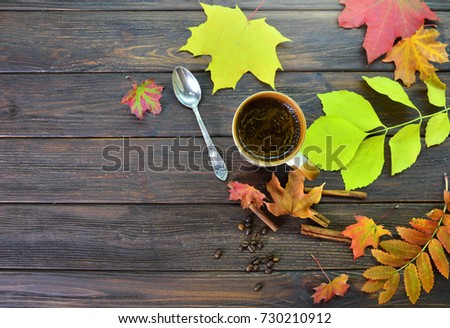 A cup of fragrant coffee on a wooden table surrounded by colorful autumn leaves background #730210912