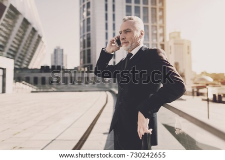 A man in a black suit is waiting for an important conversation #730242655