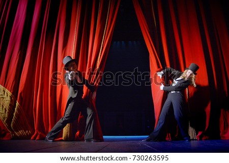 the actor opens a theater curtain Royalty-Free Stock Photo #730263595