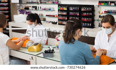 Happy american women getting their nails done at beauty salon #730274626