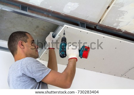 Construction worker assemble a suspended ceiling with drywall and fixing the drywall to the ceiling metal frame with screwdriver. Renovation, construction and do it yourself DIY concept. #730283404
