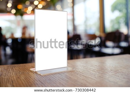 Mock up Menu frame standing on wood table in Bar restaurant cafe. space for text.