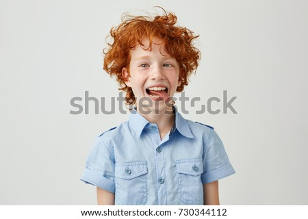Portrait of silly little ginger boy in blue shirt with wild hair mowing eyes, smiling and showing tongue in camera,making funny faces. #730344112