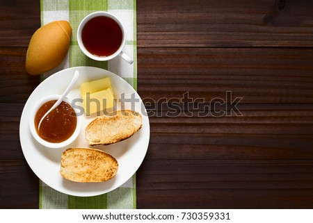 Toasted bread roll halves with butter, peach jam and tea on the side, photographed overhead on dark wood with natural light #730359331