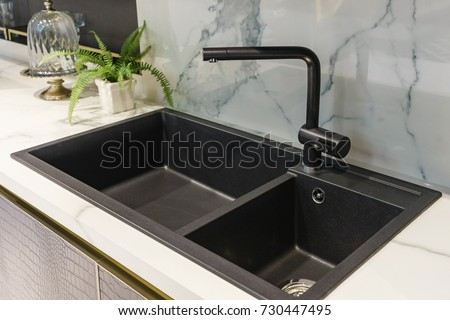 Black kitchen sink and Tap water in the kitchen. The interior of the kitchen room of the apartment. Built-In Appliances. Kitchen Appliance. Domestic Appliances #730447495