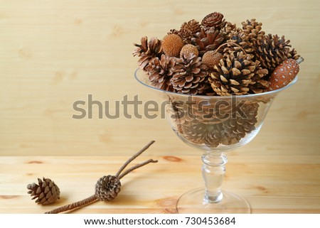 Many different type and different size of natural dry pine cones in a glass compote, wooden background with free space for text and design
