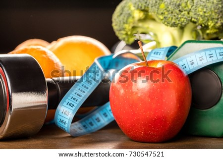 close up view of healthy food, measuring tape and dumbbells, healthy living concept #730547521